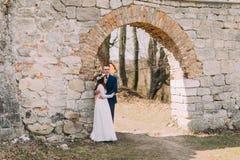Nygift personpar poserar på den gamla förstörda porten av den forntida barocka slottväggen Arkivfoto