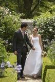 Nygift personpar som går i parkera Fotografering för Bildbyråer