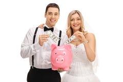Nygift personpar som sätter pengar in i en piggybank Royaltyfri Foto