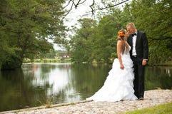 Nygift personpar vid sjön Fotografering för Bildbyråer