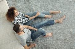 Nygift personparsammanträde på en matta i en ny vardagsrum Arkivfoton