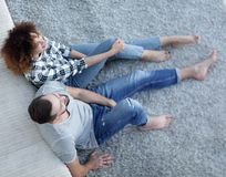 Nygift personparsammanträde på en matta i en ny vardagsrum Royaltyfri Fotografi