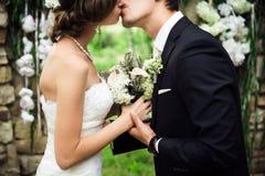 Nygifta personer är kyssande försiktigt arkivbild