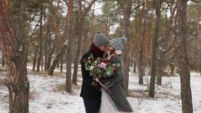 Nygifta personer ansar och brudkramkyssen och värme sig i snöig pinjeskog under snöfall i ultrarapid Barn