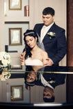 Nygifta personer. Brud som spelar pianot royaltyfri fotografi