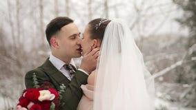 Nygifta personer brudgum och brudkramkyss och slaglängd i snöig vintergrön skog under snöfall i ultrarapid