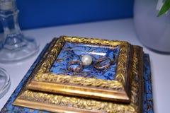 Nygifta personer för guld- cirklar är bredvid vita pärlor Arkivfoton