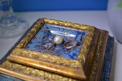 Nygifta personer för guld- cirklar är bredvid vita pärlor Royaltyfri Fotografi