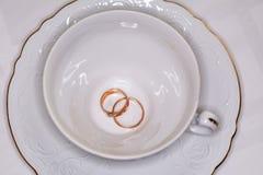 Nygifta personer för guld- cirklar och tom vit kopp Arkivbild