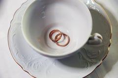 Nygifta personer för guld- cirklar och tom vit kopp Royaltyfri Bild