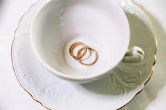 Nygifta personer för guld- cirklar och tom vit kopp Royaltyfri Foto