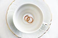 Nygifta personer för guld- cirklar och tom vit kopp Royaltyfri Fotografi