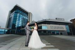 Nygifta personer framme av den höga blåa byggnaden Arkivfoto