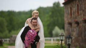 Nygifta personer går i den gamla staden Brudbrudgum som grenslas som en häst lager videofilmer