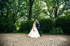 Nygifta personer går i parkera på bröllopdagen Bruden och brudgummen Enjoying på bröllopdagen arkivfoton