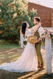 Nygifta personer i cowboystil som står och kramar på ranch fotografering för bildbyråer