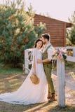 Nygifta personer i cowboystil som står och kramar på ranch royaltyfri fotografi