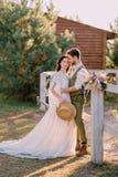 Nygifta personer i cowboystil som står och kramar på ranch arkivbilder