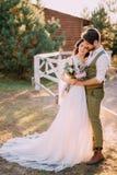 Nygifta personer i cowboystil som står och kramar på ranch arkivbild