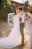Nygifta personer i cowboystil som står och kramar på ranch royaltyfri bild