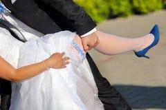 Nygifta personer i soligt sken för kram utomhus Arkivbild