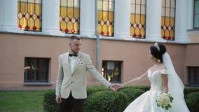 Nygifta personer kramar och tycker sig om på deras gifta sig dag arkivfilmer