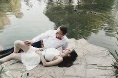 Nygifta personer ligger på stenen nära sjön med änder royaltyfri fotografi