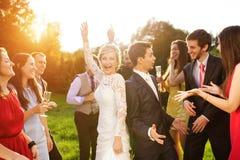 Nygifta personer med gästen på deras trädgårds- parti arkivfoton