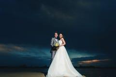 Nygifta personer på flodbanken på natten Royaltyfri Bild