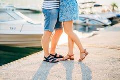 Nygifta personer på kajen Lägger benen på ryggen närbild arkivbild