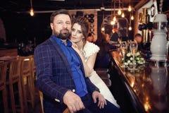 Nygifta personer sitter i ett kafé på stången royaltyfria foton