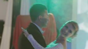 Nygifta personer som dansar deras första bröllopdans i a lager videofilmer