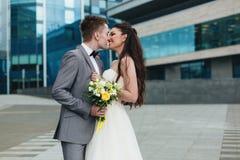 Nygifta personer som framme kysser av byggnaden Royaltyfri Foto