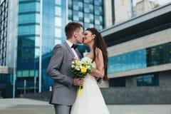 Nygifta personer som framme kysser av byggnaden Royaltyfria Bilder