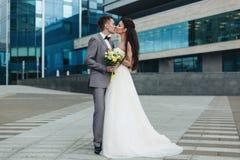 Nygifta personer som framme kysser av byggnaden Royaltyfri Bild