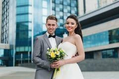 Nygifta personer som framme ler av byggnaden Royaltyfri Bild