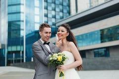 Nygifta personer som framme skrattar av byggnaden Fotografering för Bildbyråer