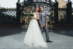 Nygifta personer som framme står av portarna Arkivbild
