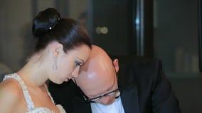 Nygifta personer som klipper bröllopstårtan stock video