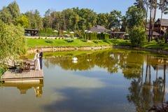 Nygifta personer som kramar, medan stå på träpir nära sjön på solen arkivbild