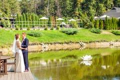 Nygifta personer som kramar, medan stå på träpir nära sjön på solen royaltyfri foto