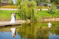 Nygifta personer som kramar, medan stå på träpir nära sjön på solen royaltyfri bild