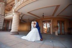 Nygifta personer som kysser att stå under balkongen royaltyfria bilder