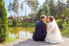 Nygifta personer som kysser, medan sitta på träpir nära sjön på sunn arkivbilder