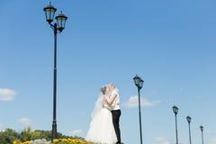 Nygifta personer som kysser mot himlen arkivbild
