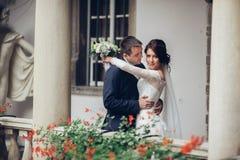 Nygifta personer som kysser och ler på deras bröllopdag på gånollan royaltyfri foto