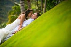 Nygifta personer som kysser på det gröna gräset royaltyfria bilder
