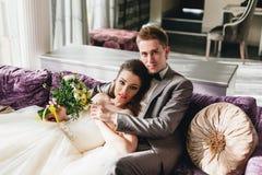 Nygifta personer som ligger på soffan Royaltyfri Foto