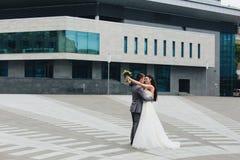 Nygifta personer som omfamnar i fron av byggnaden Arkivbilder