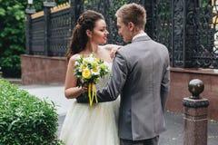 Nygifta personer som omfamnar och ler Fotografering för Bildbyråer